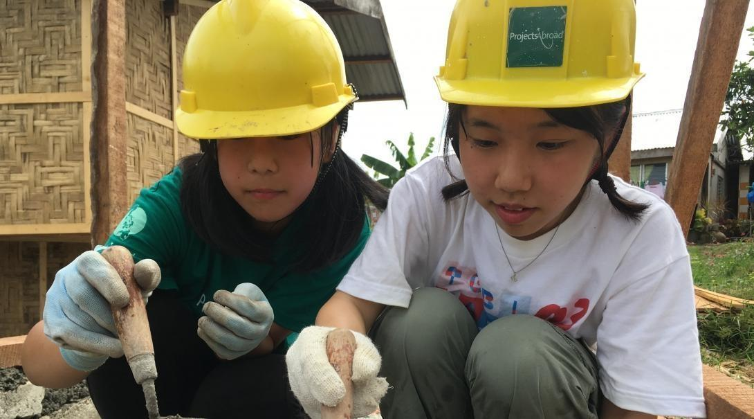 Two young volunteers helping to build up a local community